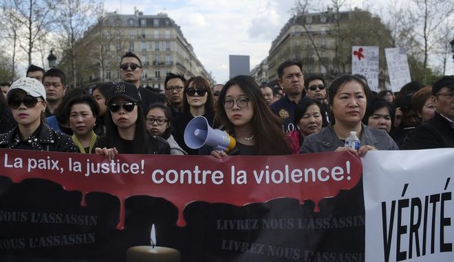 "People from the Chinese community holds a banner reading "" For peace and justice, against violence"" as they protest over the fatal shooting of Shaoyo Liu in his apartment, in Paris, Sunday, April 2, 2017. The Asian community have been protesting the death of 56-year-old Liu since Monday. Police called to Liu's building over reports of a man with a knife broke down the door of his apartment and shot him to death. Police say he attacked an officer with scissors. (AP Photo/Thibault Camus)"