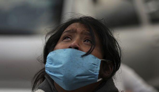 Ένα κορίτσι φορά μάσκα για προστασία από τον κορονοϊό και κοιτά ψηλά, στο Μεξικό