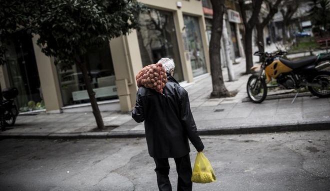 An elderly man carries groceries as walks in central Thessaloniki, Greece on March February 22, 2015. /           ,     22 , 2015.