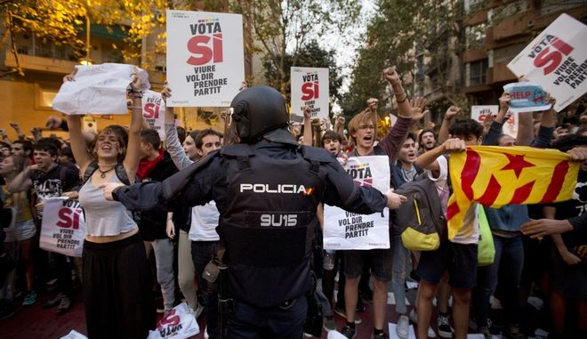 In this photo taken on Wednesday, Sept. 20, 2017, a Spanish national police officer tries to stop demonstrators protesting outside the main offices of the left wing party CUP in Barcelona, Spain. A confrontation between the central government in Madrid and independence movements in the wealthy northeastern Catalonia region has been gripping Spain for weeks. The conflict is due to come to a head on Sunday Oct. 1, 2017 when Catalonia intends to hold a regional ballot on whether to break away from the rest of Spain, despite government efforts to stop a vote being held. (AP Photo/Emilio Morenatti)