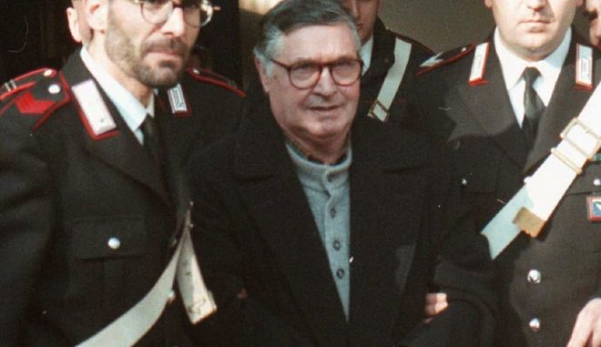 FILE - In this Jan. 16, 1996 file photo, Mafia ''boss of bosses'' Salvatore ''Toto'' Riina, center, enters handcuffed into Bologna's bunker-courtroom, escorted by Carabinieri, Italian paramiliary police, in Bologna, Italy. Italian media is reporting that Mafia boss of bosses Salvatore Toto Riina has died while serving multiple life sentences. He was 87. The justice ministry on Thursday, Nov. 16, 2017,  had allowed his family a bedside visit at a hospital Parma shortly before his death. He had been placed in a medically induced coma after his health deteriorated following two recent surgeries. (AP Photo/Gianni Schicchi, File)