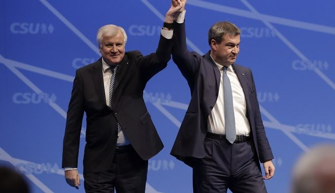Candidate for new State Governor Markus Soeder, right, and Bavarian State Governor and Chairman of German Christian Social Union party, CSU, Horst Seehofer, celebrate on the podium after voting at a party convention of the German Christian Social Union in Nuremberg, Germany, Saturday, Dec. 16, 2017. (AP Photo/Matthias Schrader)