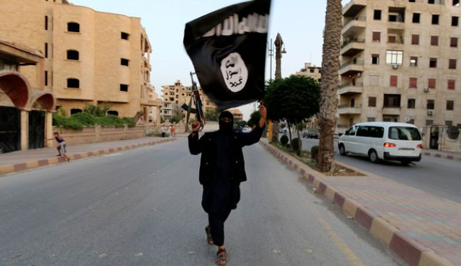 "A member loyal to the Islamic State in Iraq and the Levant (ISIL) waves an ISIL flag in Raqqa June 29, 2014. The offshoot of al Qaeda which has captured swathes of territory in Iraq and Syria has declared itself an Islamic ""Caliphate"" and called on factions worldwide to pledge their allegiance, a statement posted on jihadist websites said on Sunday. The group, previously known as the Islamic State in Iraq and the Levant (ISIL), also known as ISIS, has renamed itself ""Islamic State"" and proclaimed its leader Abu Bakr al-Baghadi as ""Caliph"" - the head of the state, the statement said. REUTERS/Stringer (SYRIA - Tags: POLITICS CIVIL UNREST TPX IMAGES OF THE DAY)"