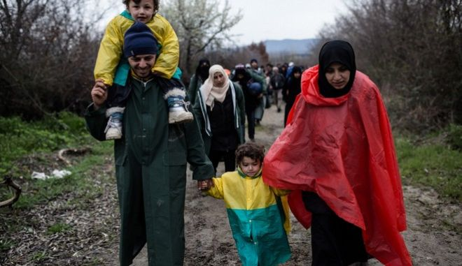 Refugees and migrants from Idomeni refugee camp start march to cross the Greek - FYROM border from an alternative route in the border area where there is no fence on March 14, 2016.
