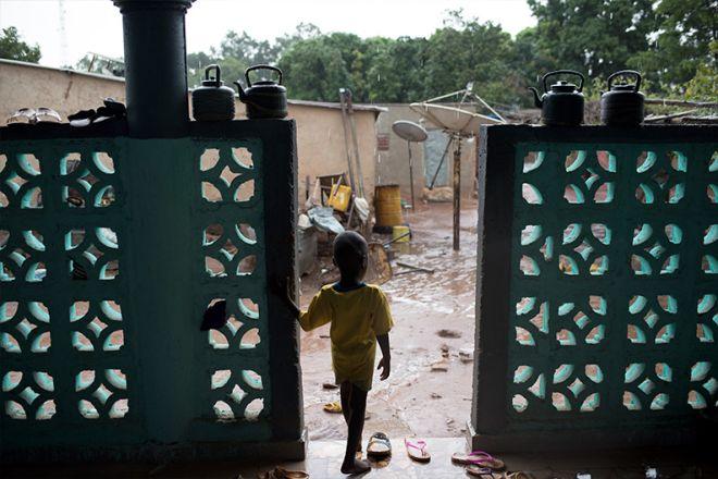 Ένα μικρό παιδί παρακολουθεί τη βροχή στο χωριό της Bougoula.