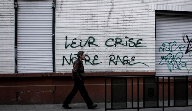 A man passes in front of a wall where a graffiti reads in French `Their Crisis, Our Rage', in Brussels, May 7, 2015 /               `  ,   `,  , 7 , 2015