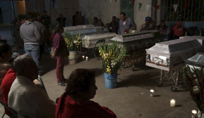 CORRECTS AGE OF BABY TO TWO MONTHS, NOT TWO YEARS - Mourners hold a wake for 11 family members who were killed inside the Santiago Apostol church during the 7.1 earthquake in the town of Atzala in Puebla state, Mexico, Wednesday, Sept. 20, 2017. According to family related to the victims who died inside the church during Tuesday's quake, the roof collapsed during a Mass held to baptize a two-month-old girl, and the only people who survived were the baby's father, the priest and the priest's assistant. (AP Photo/Pablo Spencer)