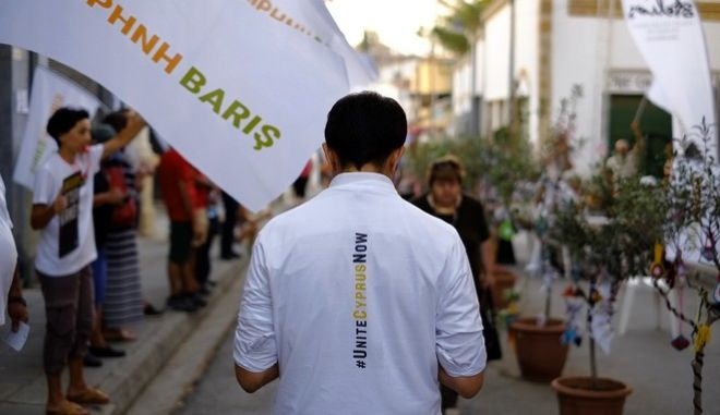 """A peace protestor with a t-shirt """"United Cyprus Now"""" takes part in a peace demonstration as people wave flags reading in Greek """"Peace"""", in Ledra crossing point inside the U.N buffer zone in central divided capital, Nicosia, Cyprus, Wednesday, July 5, 2017. President Nicos Anastasides, a Greek Cypriot, told reporters before another session of the ongoing talks in Switzerland that he expects the Turkish and Turkish Cypriot participants to """"demonstrate the same good will"""" to break the stalemate. (AP Photo/Petros Karadjias)"""