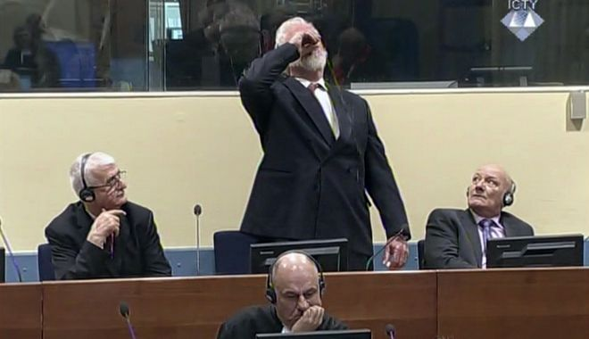 In this photo provided by the ICTY on Wednesday, Nov. 29, 2017, Slobodan Praljak brings a bottle to his lips, during a Yugoslav War Crimes Tribunal in The Hague, Netherlands. Praljak yelled,