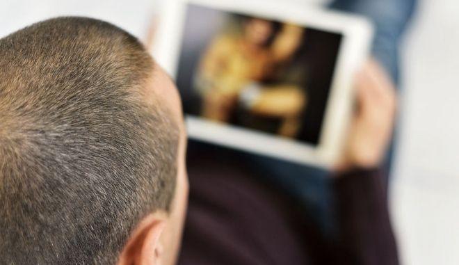 Άνδρας παρακολουθεί ερωτική ταινία στο τάμπλετ του