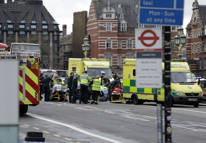 Emergency services staff provide medical attention close to the Houses of Parliament in London, Wednesday, March 22, 2017. London police say they are treating a gun and knife incident at Britain's Parliament