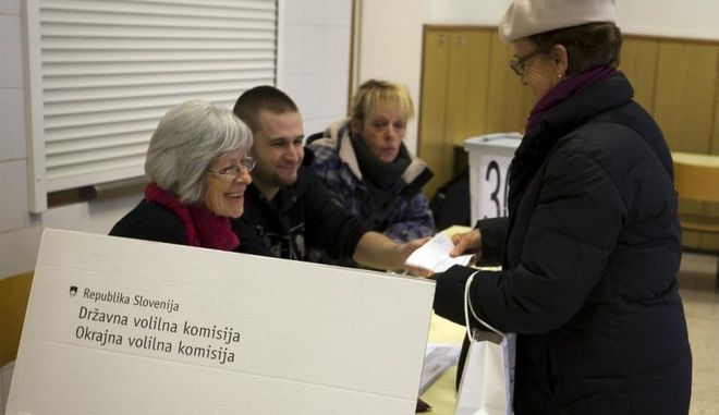 A voter is registered at a polling station in Ljubljana, Slovenia, Sunday, Dec. 20, 2015.  Slovenians held a referendum Sunday on whether to allow same-sex marriage for the first time in any of the former communist nations of Central and Eastern Europe. (AP Photo/Darko Bandic)