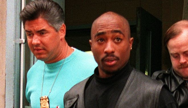 Rap star Tupac Shakur is led from the Manhattan North police precinct after being arrested in an alleged sexual attack on Nov. 19, 1993.  (AP Photo/Justin Sutcliffe)