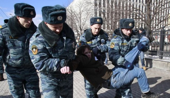 Russian police officers detain a supporter of jailed members of the punk group Pussy Riot during a protest calling for their release, in central Moscow March 8, 2013. REUTERS/Sergei Karpukhin (RUSSIA  - Tags: POLITICS CIVIL UNREST CRIME LAW)