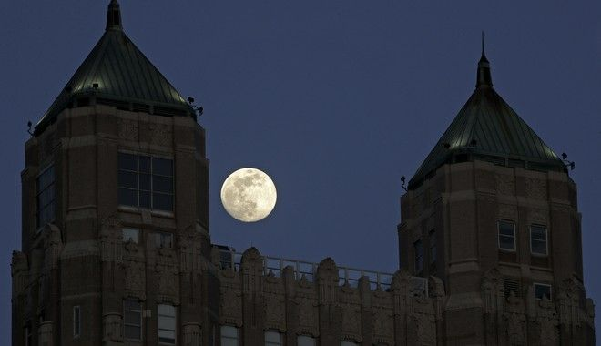 The waxing moon rises between the twin penthouses of an apartment building in downtown Kansas City, Mo., Tuesday, May 5, 2020. (AP Photo/Charlie Riedel)