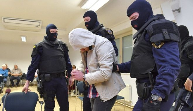 Masked police officers lead a 23-years old terror suspect into the court room in Salzburg, Austria, Tuesday, Feb. 21, 2017. The Syrian man is accused of being member of the Islamic State organization.  (AP Photo)