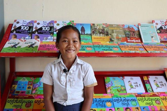 Η Bun Ny χαρούμενη μπροστά από την καινούργια βιβλιοθήκη του σχολείου της