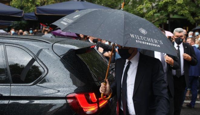 Ο Κυριάκος Μητσοτάκης με ομπρέλα του ξενοδοχείου Wiltcher's στην τελετή αποχαιρετισμού του Μίκη Θεοδωράκη