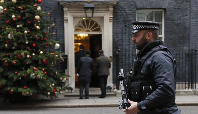 An armed police officer keeps guard at Downing Street in London, Wednesday, Dec. 6, 2017. Two men will appear in a London court to face terror charges Wednesday after reportedly plotting to assassinate British Prime Minister Theresa May. The plan, revealed to the British Cabinet on Tuesday, allegedly involved planting a bomb outside the entrance to Downing Street gates before attackers would stab the U.K. leader in the ensuing chaos. (AP Photo/Kirsty Wigglesworth)