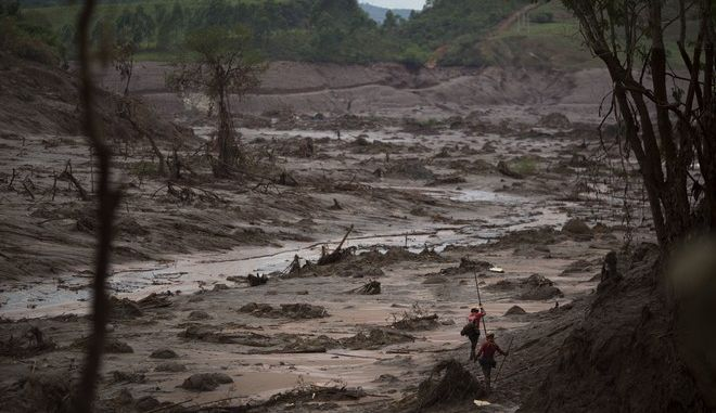 FILE - In this Nov. 8, 2015 file photo, rescue workers search for victims in Bento Rodrigues, Brazil, two days after a tsunami of mud, caused by a dam break, engulfed the town in the state of Minas Gerais. A federal judge agreed on Thursday, Nov. 17, 2016, to hear a criminal case filed against four companies and 22 people allegedly involved in last year's mine dam burst that killed 19 people and polluted hundreds of miles of rivers and streams. (AP Photo/Felipe Dana)