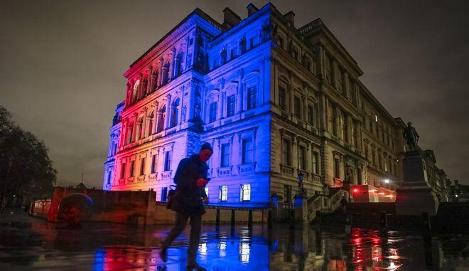 Άνδρας έξω από το φωταγωγημένο για την περίσταση  υπουργείο Εξωτερικών της Μεγάλης Βρετανίας