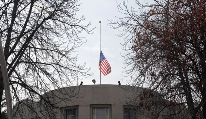 "The US embassy's flag flies at half-mast in respect for the Florida school shooting victims in Ankara, Turkey, Monday, Feb. 19, 2018. Municipality workers on Monday took down the street sign for Nevzat Tandogan Street where the U.S. Embassy is located and replaced it with one that reads ""Olive Branch Street."" (AP Photo/Burhan Ozbilici)"
