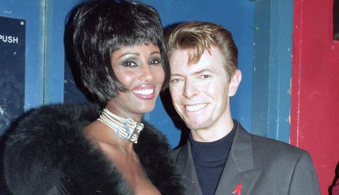 """British rock singer David Bowie and his wife, supermodel Iman, are seen backstage at the Prince of Wales """"Concert of Hope"""" to mark World AIDS Day at London's Wembley Arena, on December 1, 1993.  (AP Photo/Gill Allen)"""