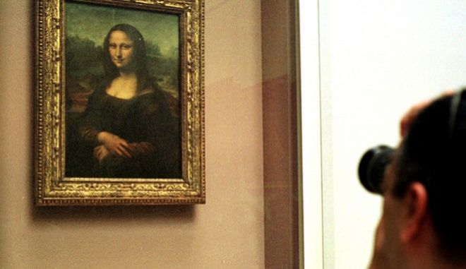 **FILE** A man takes a photograph of The Mona Lisa painting, behind a protective glass, in the Louvre museum in Paris in a Monday April 26, 2004 file photo.  Mona Lisa, the woman depicted in Leonardo da Vinci's 16th century masterpiece, was either pregnant or had recently given birth when she sat for the painting, a French art expert said Wednesday, Sept. 27, 2006.(AP Photo/Amel Pain, File) *IMAGE MUST BE USED IN ITS ENTIRITY*