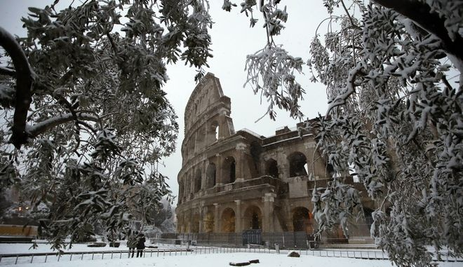 People look at the ancient Colosseum after a snowfall in Rome, Monday, Feb. 26, 2018. (AP Photo/Alessandra Tarantino)