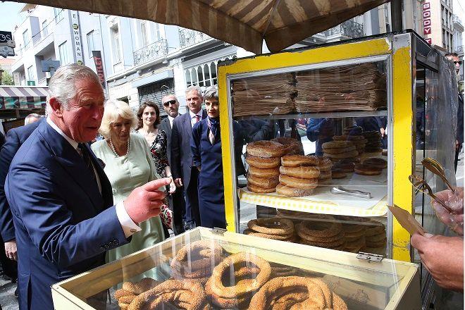 Ο Πρίγκιπας Κάρολος και η σύζυγός του Καμίλα, Δούκισσα της Κορνουάλης, αγοράζουν κουλούρι από πλανόδιο πωλητή στην Ερμού