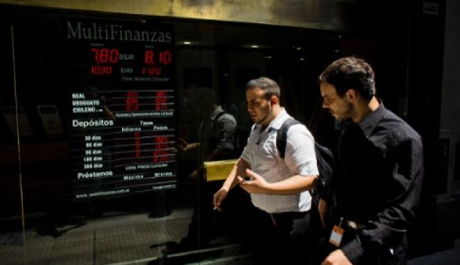 People walk by a sign indicating the exchange rate between the Argentine peso and the U.S. dollar in Buenos Aires, Argentina, Thursday, Jan. 23, 2014. Argentina's peso has plunged just over 17 percent in the last two days against the U.S. dollar, and economic analysts expect inflation to hit 30 percent this year. (AP Photo/Victor R. Caivano)