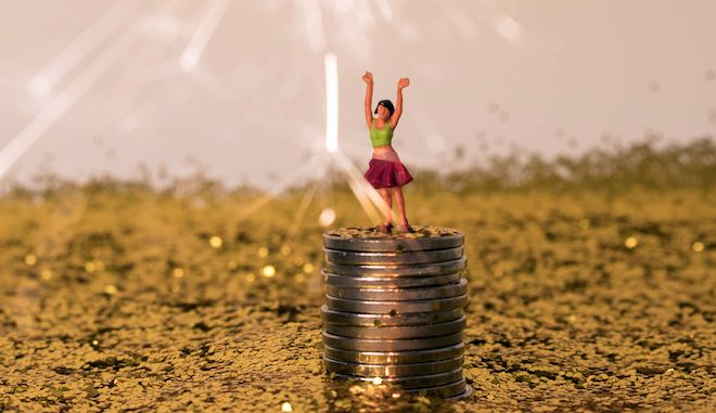 Woman in pile of gold. Miniature girl is happy with her savings, wealth, earnings, or finance. Winning a big jackpot. Money goals for 2020. Big spender or high roller.