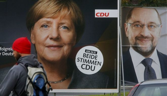 A man walks by election posters of German Chancellor Angela Merkel, left, and her challenger Martin Schulz from the Social Democrats in Frankfurt, Germany, Wednesday, Sept. 20, 2017. German elections will be held on upcoming Sunday. (AP Photo/Michael Probst)