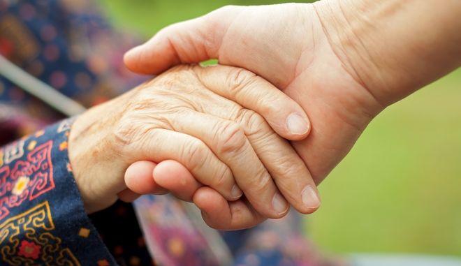 Γιατρός κρατά από το χέρι ηλικιωμένο