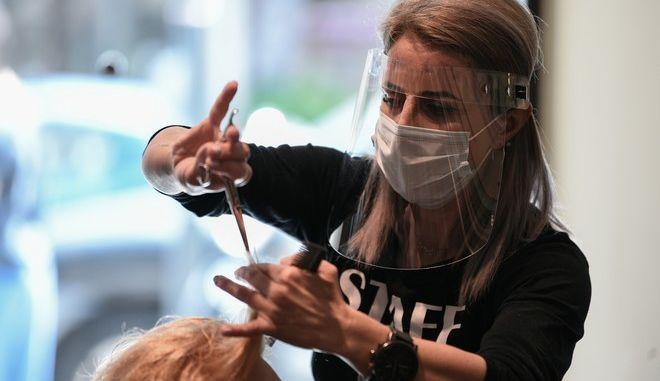 Κομμώτρια με μάσκα εν ώρα εργασίας
