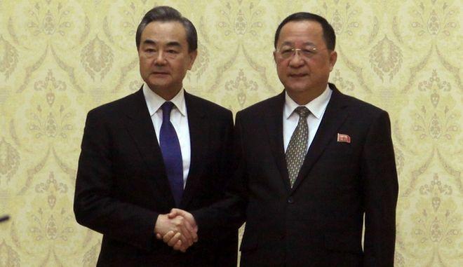 Ο Βορειοκορεάτης ΥΠΕΞ Ρι Γιονγκ (δεξιά) σε χειραψία με τον Κινέζο ομόλογό του Ουάνγκ Γι (αριστερά)