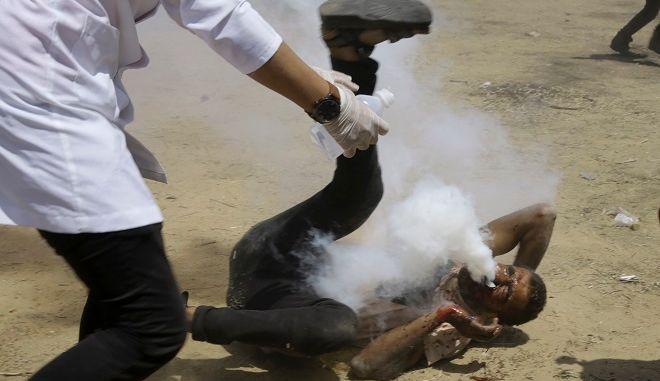 Παλαιστίνιος τραυματιοφορέας τρέχει για να βοηθήσει διαδηλωτή, ο οποίος δέχθηκε στο στόμα ένα δακρυγόνο που εκτόξευσαν Ισραηλινοί στρατιώτες κοντά στη λωρίδα της Γάζας, εκεί όπου συνορεύει με το Ισραήλ, ανατολικά του Καν Γιουνίς.