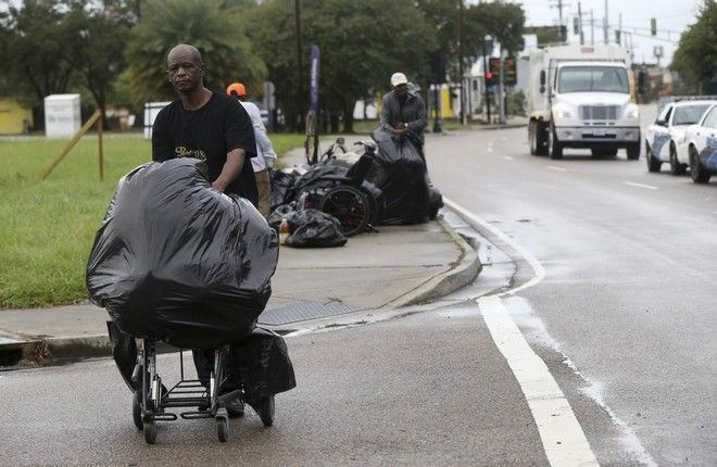 Homeless people move along with their belongings as sanitation employees perform a homeless sweep in New Orleans, in advance of approaching Hurricane Nate, Saturday, Oct. 7, 2017. (AP Photo/Gerald Herbert)