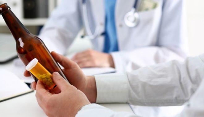 Γιατρός κρατά μπουκάλι με αλκοόλ και χάπια