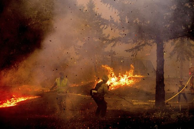 Firefighters work to save the Louis Stralla Water Treatment Plant as the Glass Fire burns in St. Helena, Calif., Sunday, Sept. 27, 2020. (AP Photo/Noah Berger)