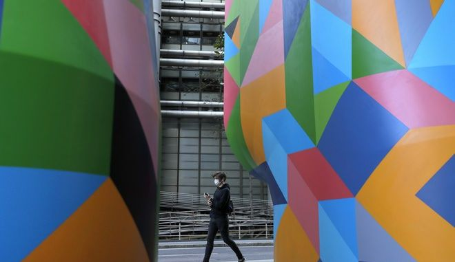 A man wears a face mask as he passes decorated air vents as part of the London Mural Festival in the City of London, Monday, Sept. 28, 2020. Lawmakers and scientists have criticized Johnson's Conservative government for problems with the national test-and-trace program that was supposed to help control the spread of the disease and reduce the need for limits on social interactions. (AP Photo/Kirsty Wigglesworth)