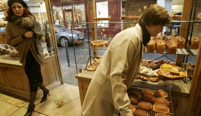 """**FOR USE WITH AP LIFESTYLES**   A customer enters Poilane Bakery as an employee displays a rack  of pain au chocolats in this Thursday, Dec. 6, 2007 photo in Paris. Literally translated as """"bread with chocolate,"""" the pain au chocolat is a typical French breakfast food, perfect with a steaming bowl of cafe au lait or as an after-school snack for hungry children. Apollonia Poilane, a third-generation baker and the CEO of Poilane bakeries, says that the butter is what makes French pain au chocolat so much better than the so-called chocolate croissant.     (AP Photo/Christophe Ena)"""