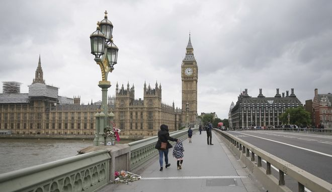 Pedestrians walk a flower tribute behind newly installed barriers on Westminster Bridge in London, Monday, June 5, 2017. Police arrested several people and are widening their investigation after a series of attacks described as terrorism killed several people and injured more than 40 others in the heart of London on Saturday. (AP Photo/Tim Ireland)