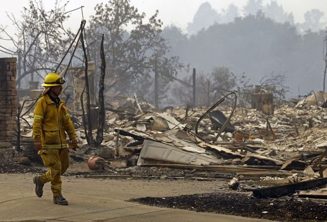 A fireman looks for hotspots in the Fountaingrove area on Monday, Oct. 9, 2017, in Santa Rosa, Calif. Wildfires whipped by powerful winds swept through Northern California early Monday, sending residents on a headlong flight to safety through smoke and flames as homes burned. (AP Photo/Ben Margot)