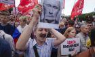 Οι διαδηλωτές κρατούν ένα πορτρέτο του Βλαντιμίρ Πούτιν με το σύμβολο «Έχουμε κουραστεί από αυτόν» , Τετάρτη 24 Ιουλίου 2019