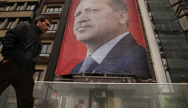 """A man walks in central Istanbul's Taksim Square, backdropped by a poster of Turkish President Recep Tayyip Erdogan,Tuesday, March 14, 2017. In a new verbal attack, Erdogan has called Germany and the Netherlands """"bandit states"""" that are harming the European Union amid Turkey's growing tensions with the two countries over Turkish ministers' plans to hold campaign meetings there. (AP Photo/Lefteris Pitarakis)"""