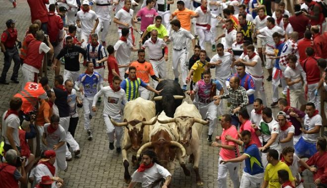 Revellers run with a Puerto de San Lorenzo fighting bull led by steers during the third running of the bulls at the San Fermin Festival, in Pamplona, northern Spain, Sunday, July 9, 2017. Revellers from around the world flock to Pamplona every year to take part in the eight days of the running of the bulls. (AP Photo/Alvaro Barrientos)