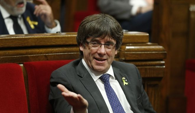 Catalan President Carles Puigdemont gestures during a session inside the Catalan parliament in Barcelona, Spain, Friday, Oct. 27, 2017. Catalan separatist lawmakers have filed a motion to hold a vote in the upcoming regional parliament session on whether to establish a republic independent of Spain. (AP Photo/Manu Fernandez)