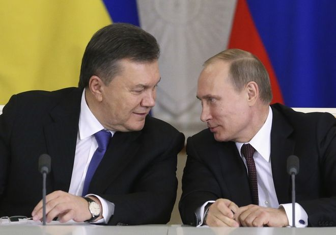Russia's President Vladimir Putin (R) looks at his Ukrainian counterpart Viktor Yanukovich during a signing ceremony after a meeting of the Russian-Ukrainian Interstate Commission at the Kremlin in Moscow, December 17, 2013. Russia threw Ukraine an economic lifeline on Tuesday, agreeing to buy $15 billion of Ukrainian debt and to reduce the price its cash-strapped neighbor pays for vital Russian gas supplies by about one-third. REUTERS/Sergei Karpukhin (RUSSIA - Tags: POLITICS BUSINESS) - RTX16MDC