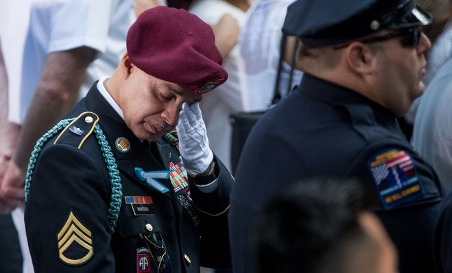 A man becomes emotional during a moment of silence during a ceremony for the 15th anniversary of the attacks on the World Trade Center at the National September 11 Memorial, in New York, Sunday, Sept. 11, 2016. (AP Photo/Andrew Harnik)